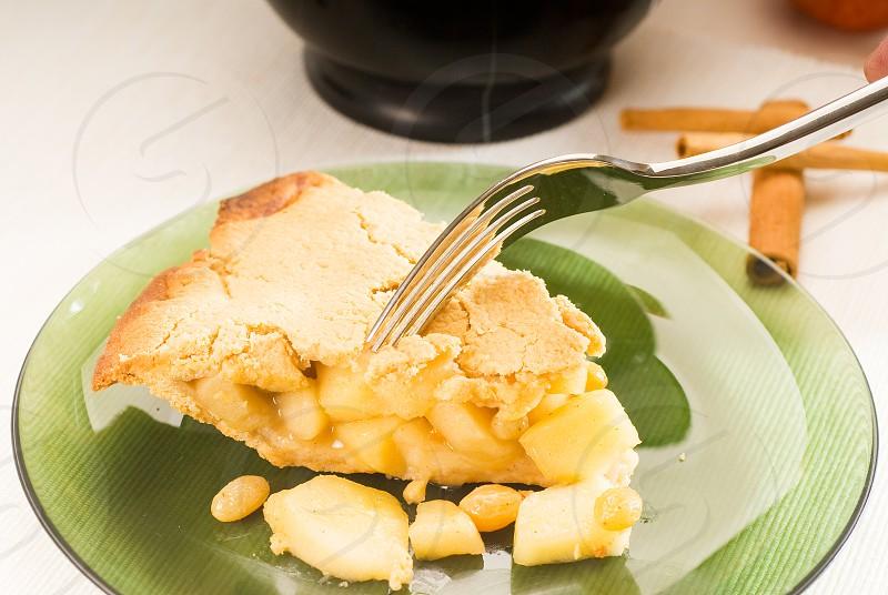 fresh homemade apple pie over green glass dish macro colseup eating  with fork photo