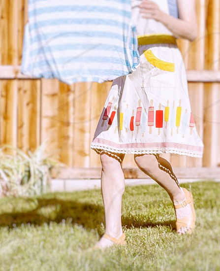 Woman hanging laundry.  Bright light retro apron spring colors.  Exterior photo