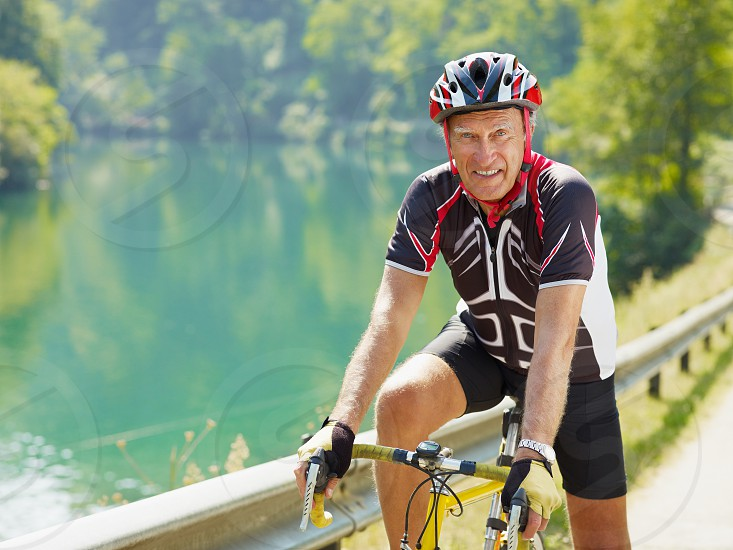 senior; man; bicycling; bicyclist; cyclist; smiling; biking; portrait; adults; active seniors; senior adult; senior man; mature; male; one person; people; 60s; 65-70 years; 70s; Caucasian; three quarter length; sports clothing; happy; happiness; looking at camera; riding; vehicle; transportation; bicycle; helmet; outdoors; road; water; leisure; retirement; retiree; sports; biker; bike riding; cycling; road bike; healthiness; wellness; physical fitness; exercising; recreation; copy space photo