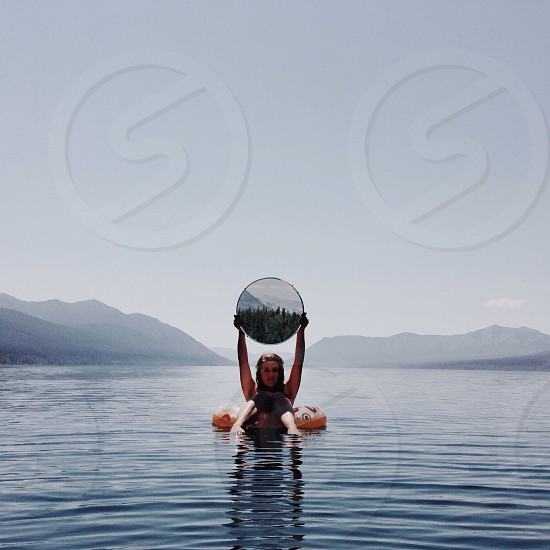 mountain lake with woman in float with round mirror photo