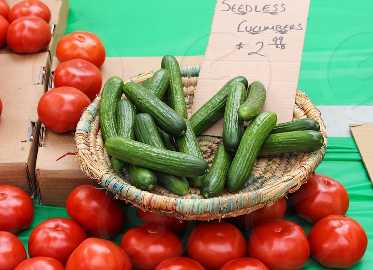 green cucumbers in brown wicker tray beside red tomatoes photo