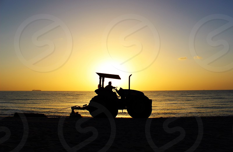 Silhouette tractor job sand erosion morning am early photo