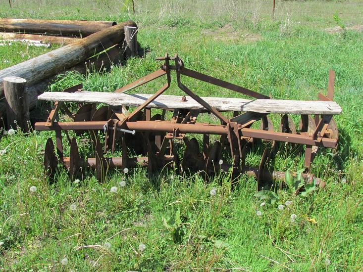 Old rusty vintage antique disc plow. Farming crops farm planter planting grass. Machinery rust photo