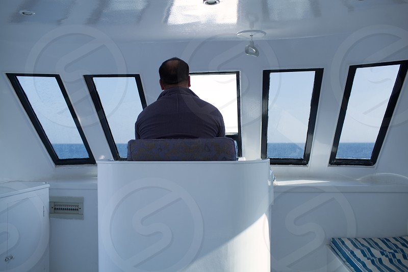 Man navigating a boat sitting in the captains chair during a cruise overlooking the ocean ahead view from behind photo
