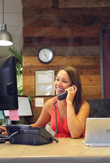 woman in orange scoop neck tank top holding black office phone photo