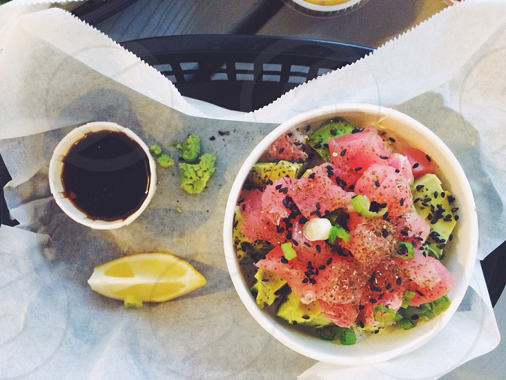 Tuna poke bowl over coconut rice and steamed spinach.  Fresh vibrant healthy food served picnic style. A delicious dinner!  photo