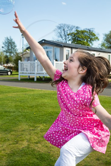 Little girl laughing and leaping for a bubble. photo