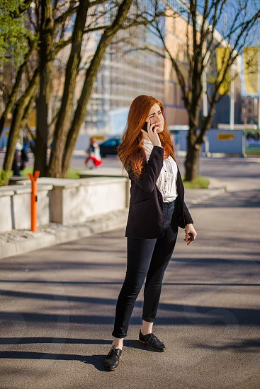 Business woman standing on the street and talking to phone photo