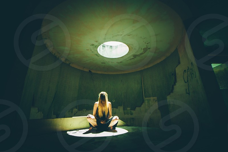 woman squatting by the white light in a room photo