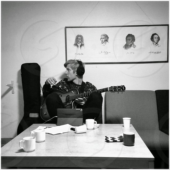 grayscale photo of person wearing long sleeve shirt black headphones and jeans holding cutaway acoustic guitar sitting next to guitar bag in front of tablet placed on square table photo