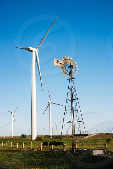 wind turbines alternative energy contrast old windmill cattle ranching  photo