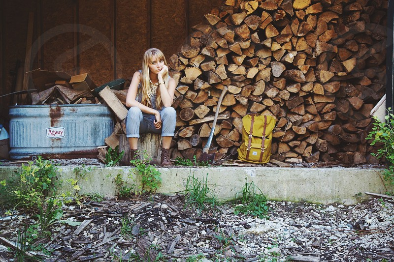 woman in denim jeans and leather boots sitting in front of woodpile photo