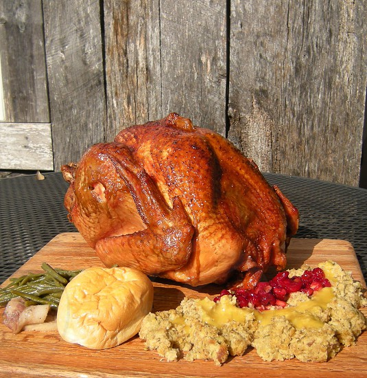 Turkey dinner with smoked turkey dressing cranberries gravy green beans potatoes roll on wood background square version photo