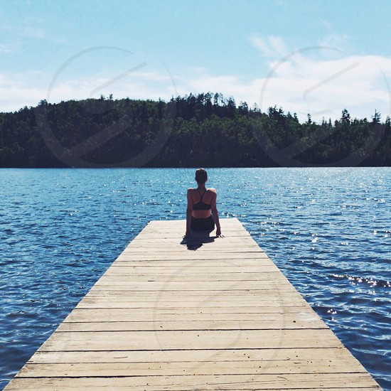 woman sitting on wooden dock by lake photo