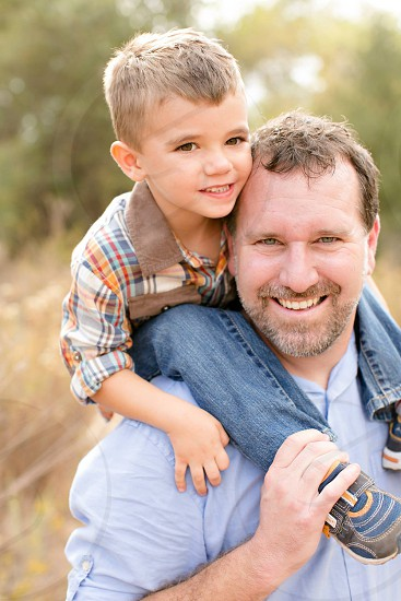 man with blue shirt holding child photo