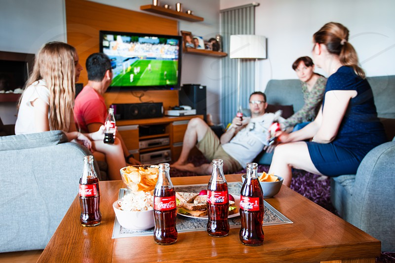 Lublin / Poland - May 12 2018: Friends enjoying watching football game on TV drinking cold drinks and eating snacks talking and spending time together. Real people authentic situations photo