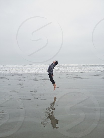 person in gray jacket jumping on water at the beach photo