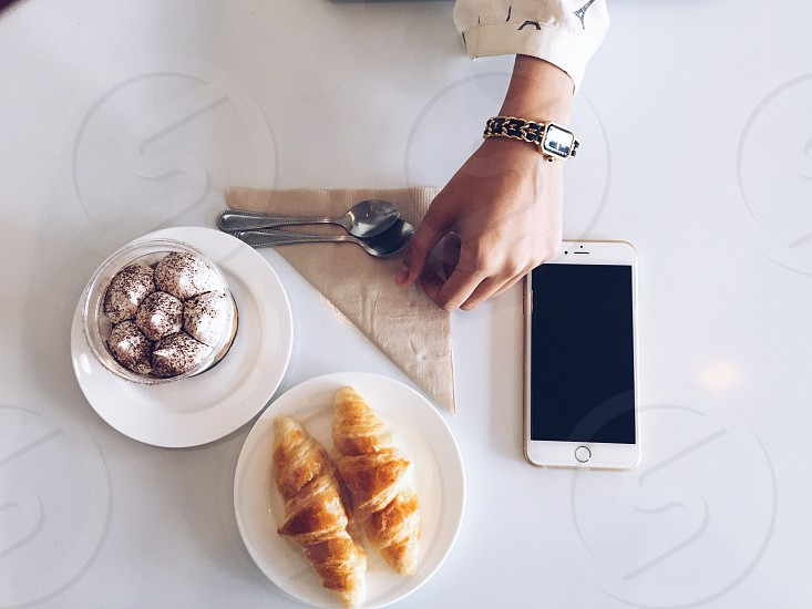 2 croissants on white ceramic plate  beside white ceramic plate with 6 round gray pastries photo