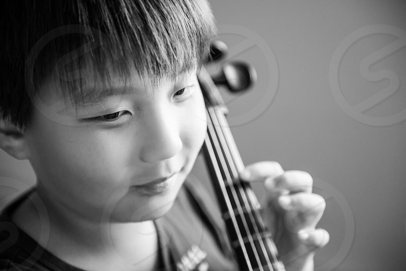 gray scale image of boy playing cello photo