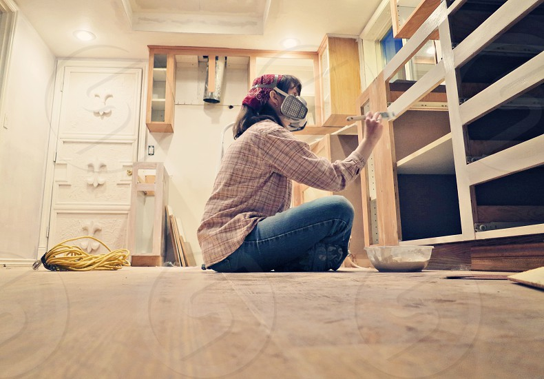 woman in gas mask blue jeans and red white button down shirt seated and painting white shelf photo