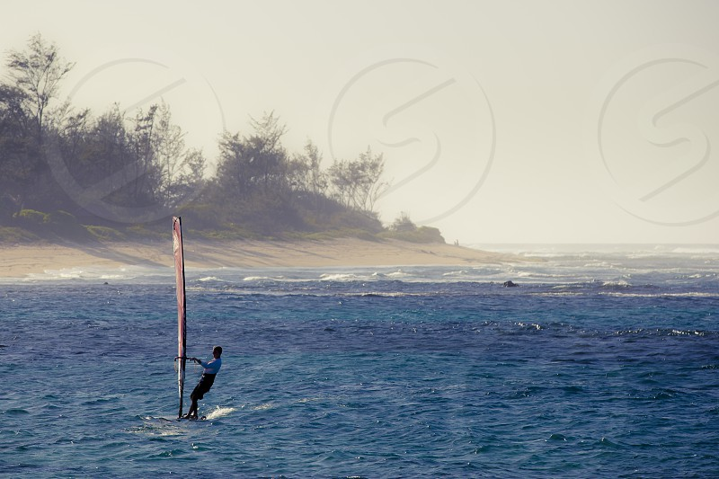man on white and brown windsurfing board on calm sea photo