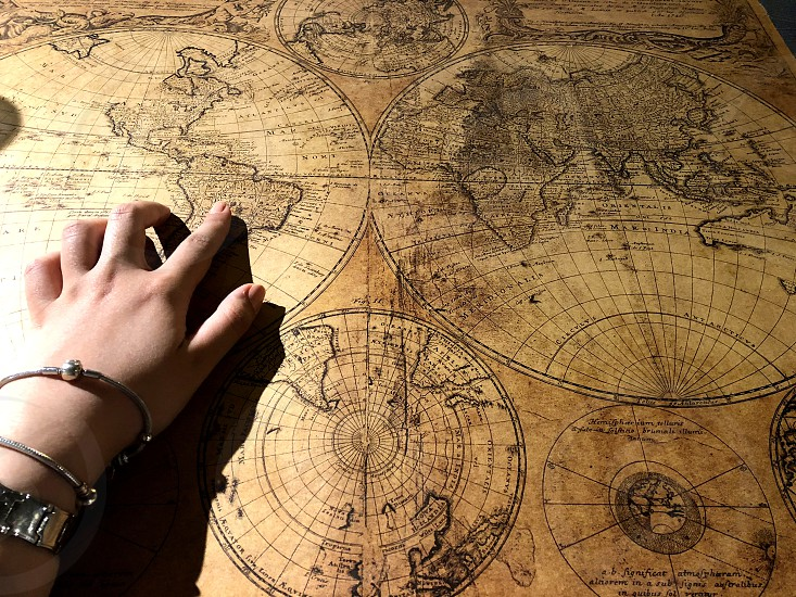 Tour operator. Hand of a young girl and historical maps. Choose the historic route. Travel back in time. photo