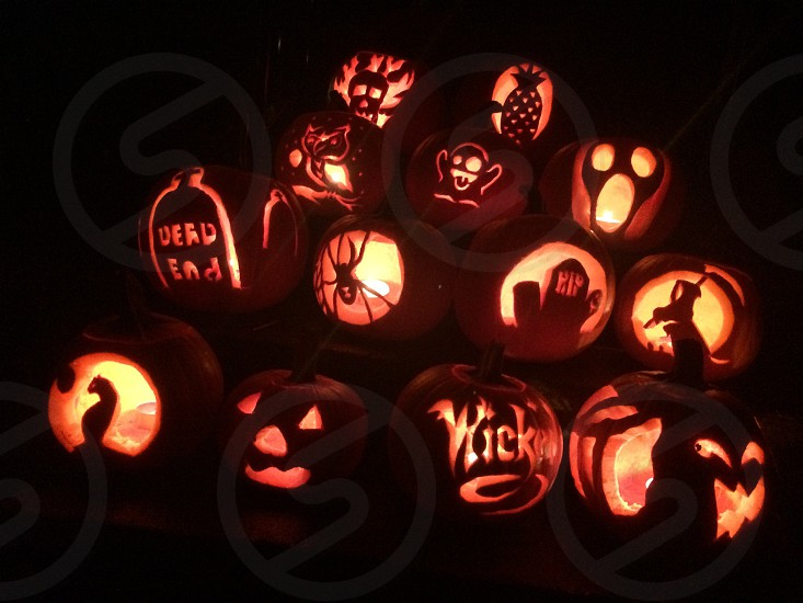 photo of purple and black jack o lantern with wicked engrave grim reaper and skull pile together photo