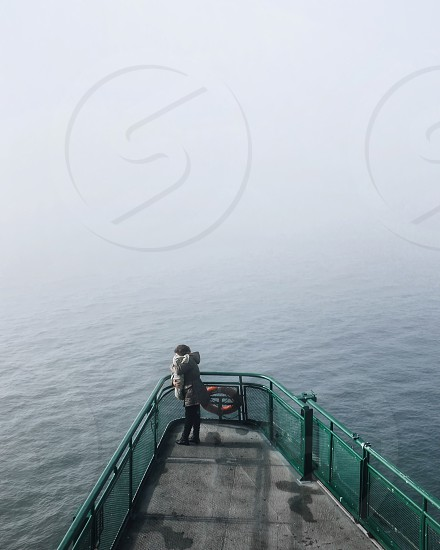 person standing on bow of ship on sea with fogs during golden hour photo