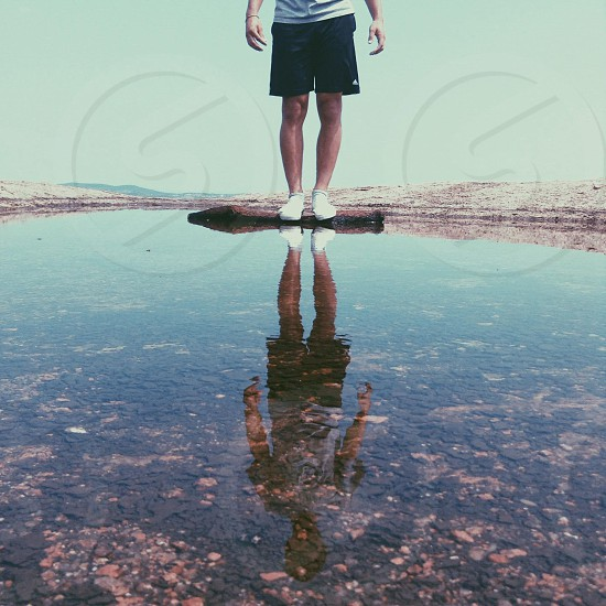 man in black board shorts standing on rock photo