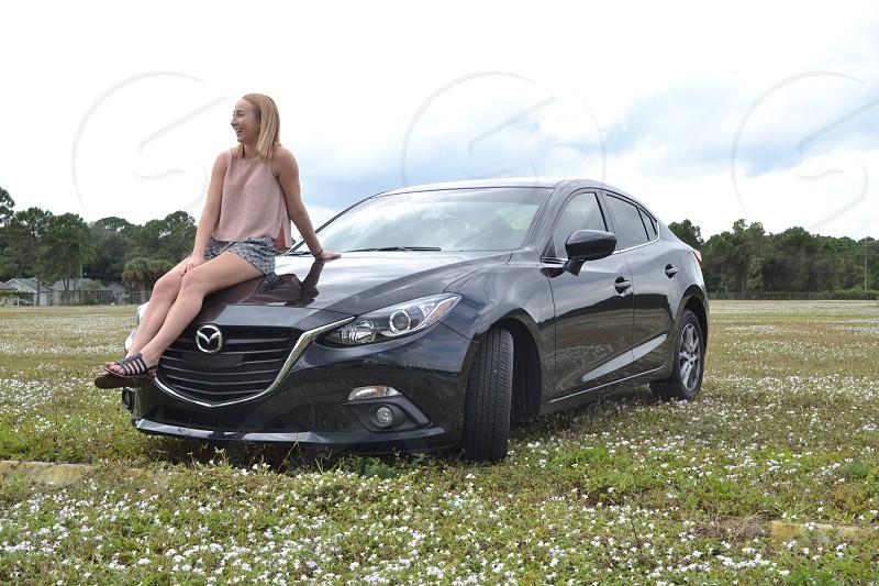 woman sitting on car hood during daytime photo