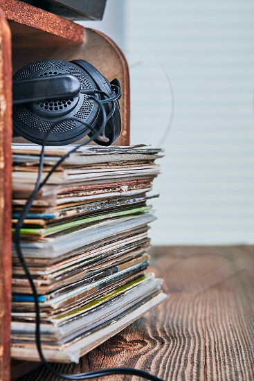 Stack of black vinyl records and headphones on the top. Candid people real moments authentic situations photo