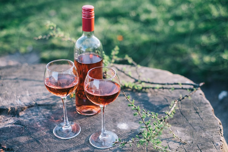 2 wine glasses and clear and red wine bottle with brown liquid inside on top of gray tree stump photo