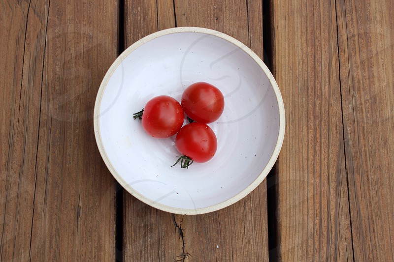 3 red cherry tomatoes in white ceramic bowl on brown wooden platform photo