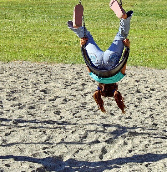 A little girl hangs backwards and upside down on a park swing her two pony tails pointing to the sand below. photo