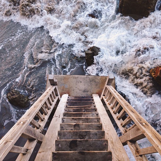 brown wooden ladder on river photo