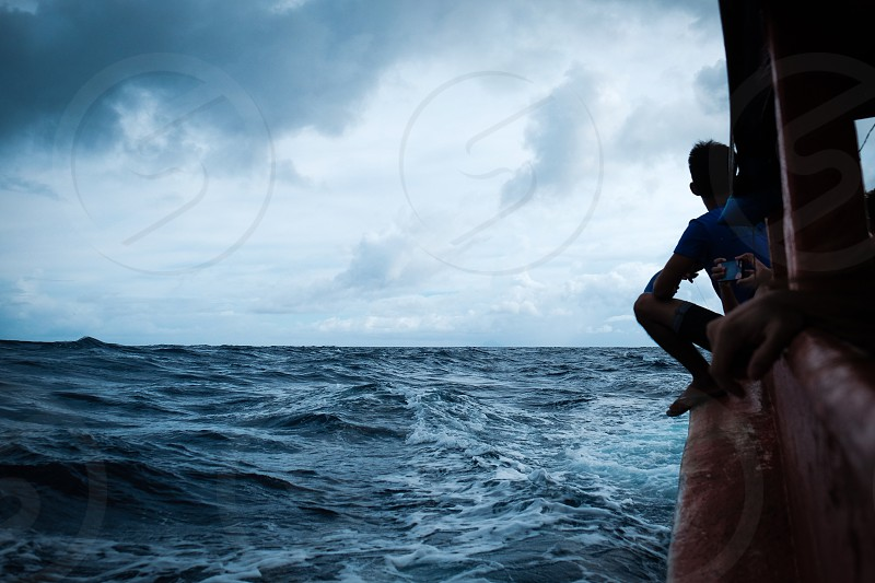 A fisherman hanging on a boat in the middle of the ocean in the Philippines photo