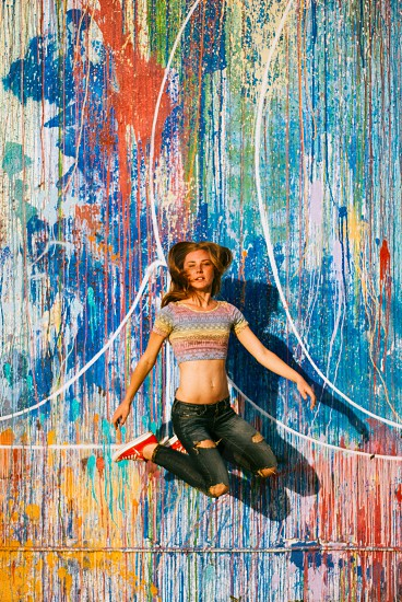 woman in blue denim distressed jeans jumping over red blue and yellow painted wall photo
