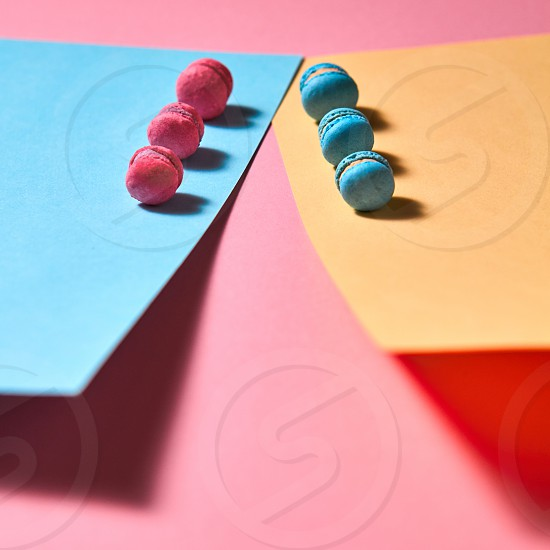 Fresh pink and blue macaroons on sheets of cardboard on a pink paper background with reflection of shadows. photo