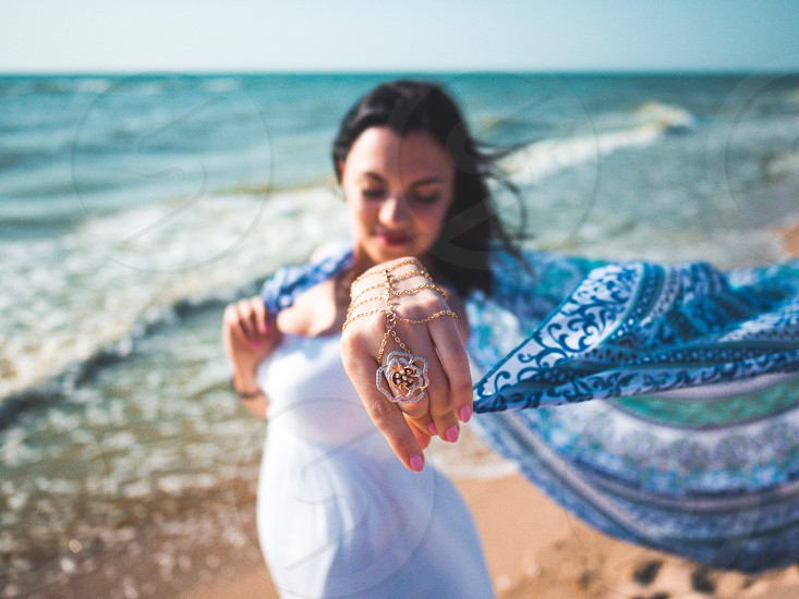 Gypsy young brunette girl wearing white maxi long dress standing near sea or ocean with mandala silk scarf in hands. Bohemian clothing style. Boho lifestyle. photo