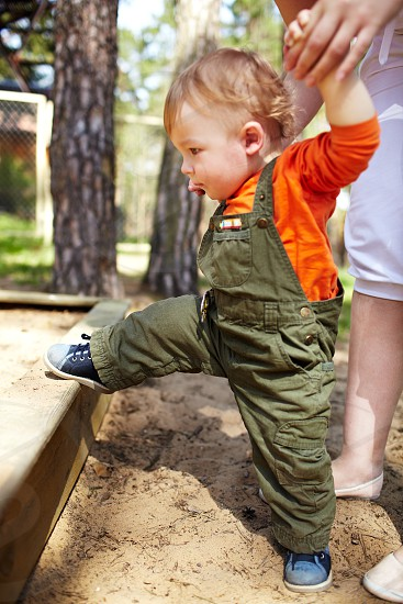 The first steps of the kid. Outdoors. photo
