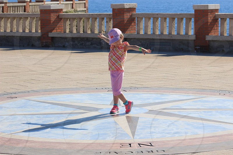 child in pink cap standing on a compass print floor beside the sea during daytime photo