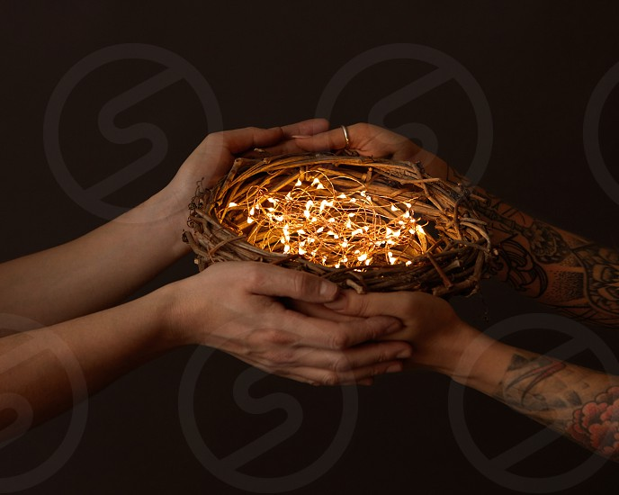 A nest of branches with bright garlands are held by male and female hands with a tattoo on a black background. Celebration photo