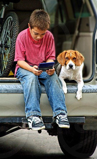 Boy plays a hand held game sitting in the back of an open van with his pet dog photo