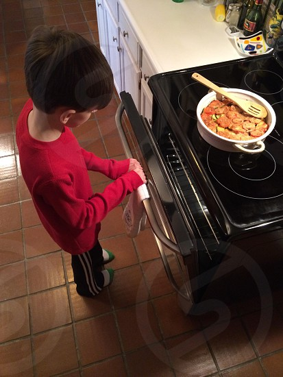 kid opening a black oven photo