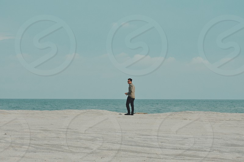 Asian man isolated alone in a vast space by the sandy beach sea with open sky photo
