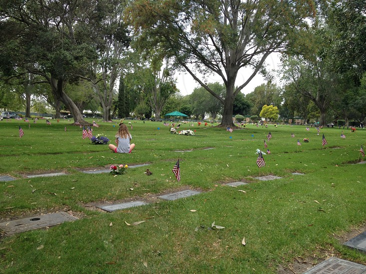 person sitting by cemetery stone photo