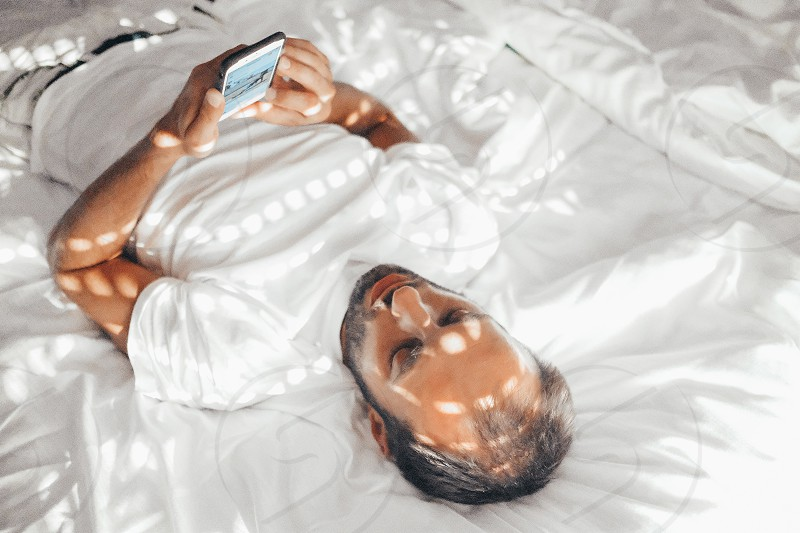 Leisure relaxation using mobile using social media bedroom white bed vibes using technology people using mobile cozy bed man bearded man natural light lights and shadows sun glare home relaxing photo