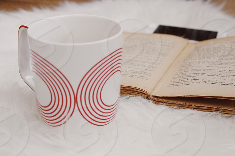 white and red ceramic mug near a brown labeled book in a white fur mat photo