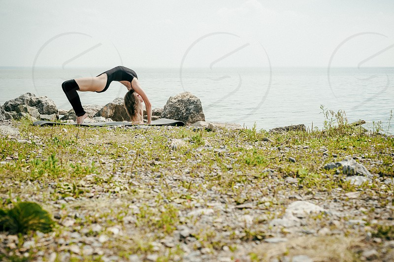 athletic woman engaged in stretching warm summer day exercise in the open air photo