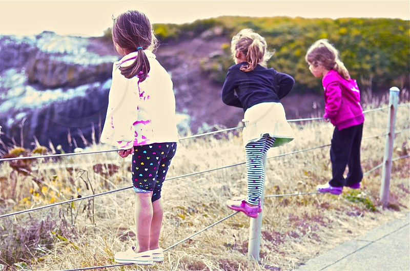 Three little girls standing on a fence - Oregon Coast photo